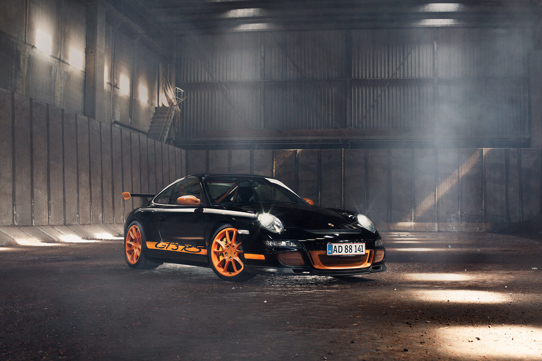 Porsche 911 GT3 RS in black and orange - photography was taking in a barn